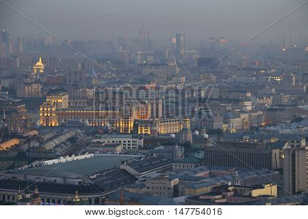Illuminated buildings and roofs in fog at summer night in Moscow, Russia, Tverskoy area