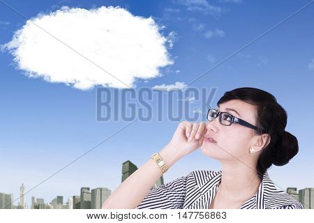 Close up of a young Asian businesswoman wearing glasses and thinking idea while looking at cloud