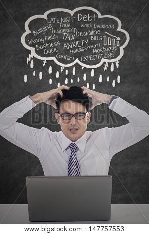 Image of a depressed worker scratching his head while thinking his problems on the cloud speech with laptop on desk