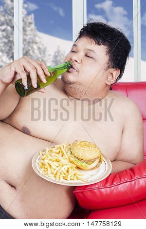 Portrait of fat man sitting on the sofa while enjoying fresh beer and junk food in winter season