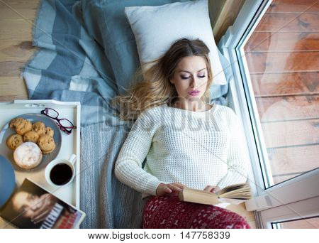 Young beautiful blonde woman with cup of coffee lying down home relaxing by the window reading book. Raining outside. Lazy day off concept.