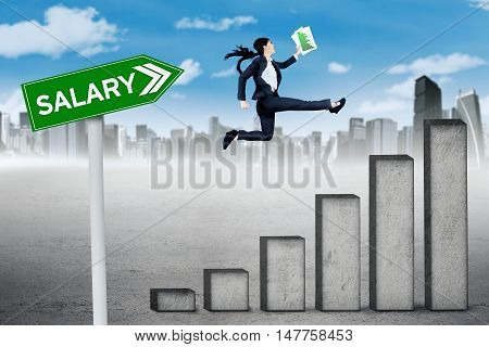 Growing salary concept. Female entrepreneur jumping above salary graph while carrying a paperwork