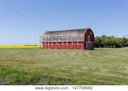 big red barn on the prairie under a clear blue sky