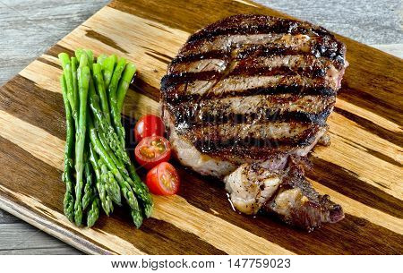 Fresh grilled rib eye steak with asparagus and cherry tomatoes ready to eat.