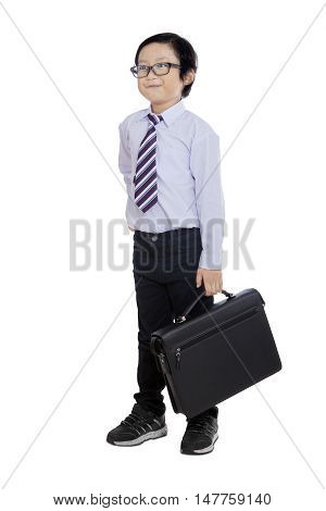 Full length of a male little entrepreneur standing in the studio while wearing formal suit and carrying a briefcase