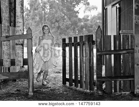 Young bride wearing gumboots under her wedding dress running through a farm gate