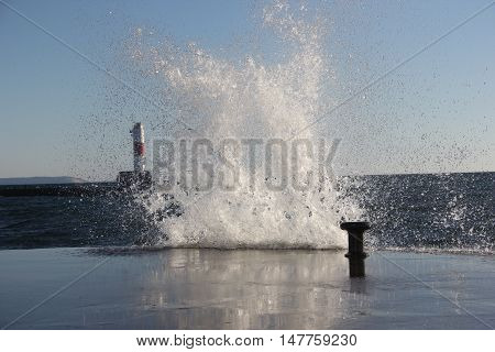 A wave splashes up on the breakwater in Frankfort, Michigan