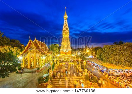 Thai people walking with lighted candles in hand around a temple candles light trail of pagoda at Phra That Phanom Temple on Visakha Bucha Day Nakhon Phanom Province Thailand