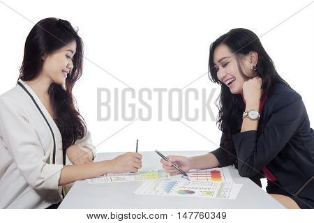 Portrait of two beautiful businesswoman discussing together while looking at financial chart on the table