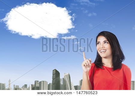 Cheerful young woman thinking idea while pointing at the cloud and smiling