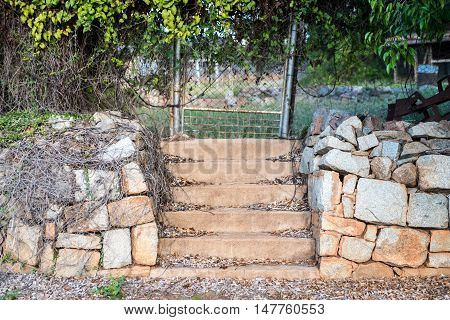 Old set of steps with rock retaining wall and fence with vine