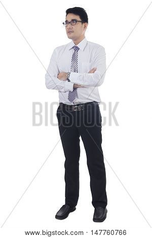 Full length of a young businessman with formal suit standing in the studio while folded hands