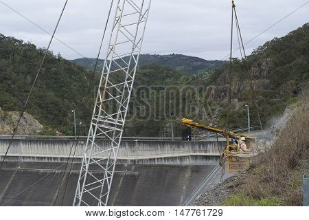 Adelaide Hills SA Australia - Sep 10 2016: Work man in a crane workbox suspended by the crane working on the the dam upgrade at Kangaroo Creek Reservoir bordering Castambul and Paracombe, South Australia