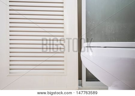 Close up white lavatory with toilet door