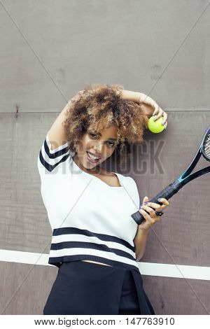 young stylish mulatto afro-american girl playing tennis smiling, sport healthy lifestyle people concept close up