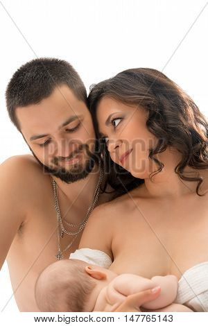 Studio portrait of young traditional family with newborn while mother breastfeeds.