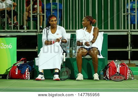 RIO DE JANEIRO, BRAZIL - AUGUST 9, 2016: Olympic champions Serena Williams (L) and Venus Willams of United States in action during doubles first round match of the Rio 2016 Olympic Games