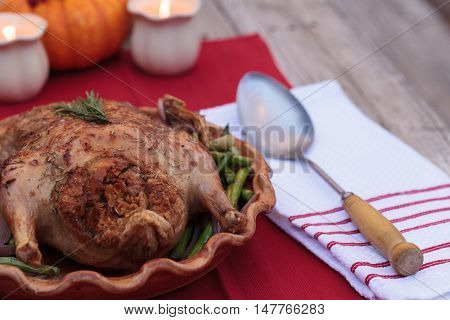 Rosemary roasted duck stuffed with bread stuffing and ringed with asparagus in a pottery dish during the holiday season.