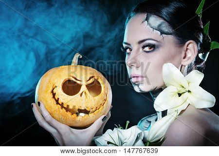 Young attractive girl with creative make-up for Halloween. Close-up portrait with a pumpkin. Mysterious image of lilies and red eyes. Jack-o'-lantern
