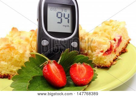 Glucose meter and pieces of fresh baked yeast cake with crumble and strawberries concept of diabetes