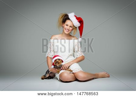 Beautiful happy girl in lace dress and red santa cap sitting with pretty yourkshire terrier in christmas hat. Studio shot over grey background. Copy space.