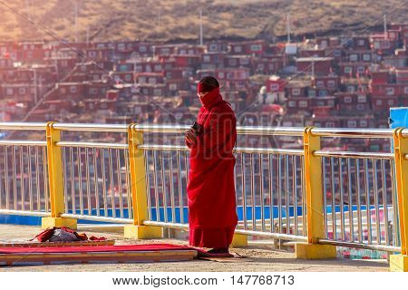 Buddhist nun prayer the sanctuary at Larung gar (Buddhist Academy) in Sichuan China. This is the public place