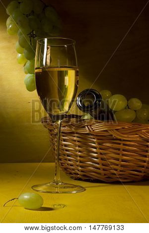 White wine in a glass and grapes on a wooden table