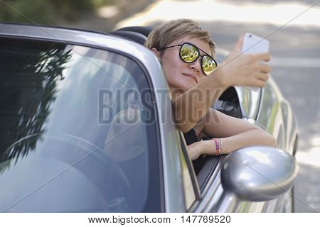 young Asian woman taking self photo in a convertible car
