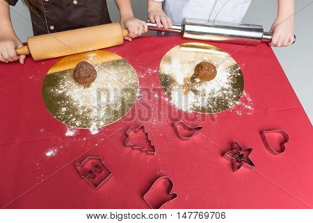 Children hands with plungers on table with dough for gingerbread and baking forms