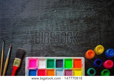 Water color palette and paintbrush on table background