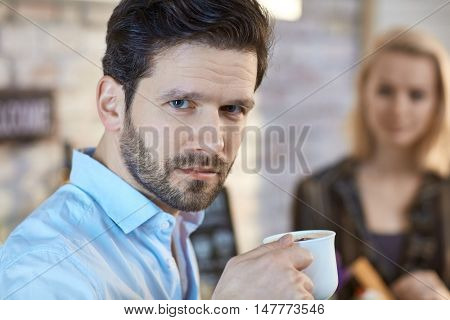 Portrait of young man drinking coffee, looking at camera.