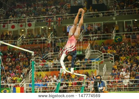 RIO DE JANEIRO, BRAZIL - AUGUST 9, 2016: Olympic champion Simone Biles of United States competes on the uneven bars at women's team all-around gymnastics at Rio 2016 Olympic Games at Rio Olympic Arena