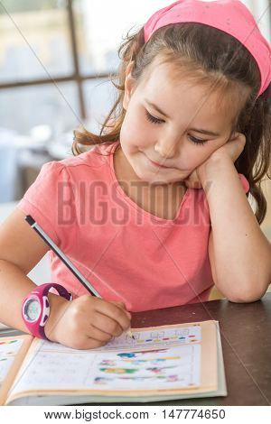 young child girl writing in notebook at home