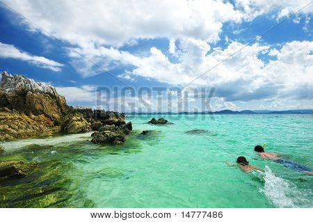 Boys snorkeling at rocky beach in Thailand. Unrecognizable faces.