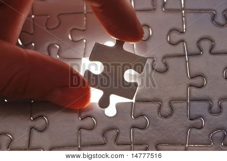 Hand placing missing puzzle piece with shallow DOF