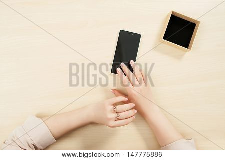 Woman using smartphone, mockup, user pov. Top view on female hands on wooden table touching phone screen and little carton box, free space