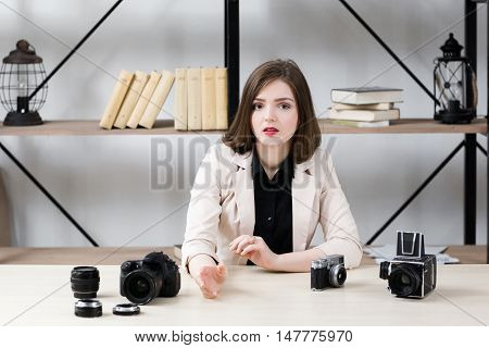Blogger reasoning about photo equipment. Young beautiful brunette talking about photographer work with different cameras on table