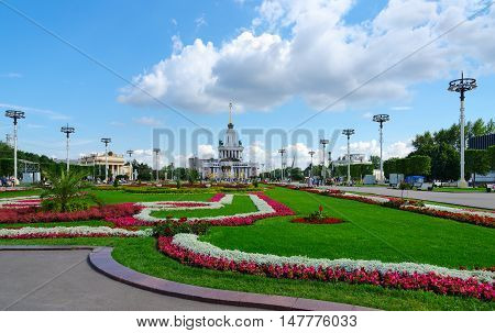 MOSCOW RUSSIA - JULY 23 2016: Unidentified people visit Exhibition of Economic Achievements in Moscow. Main Pavilion of Exhibition Center and landscaping of Exhibition of Achievements of National Economy