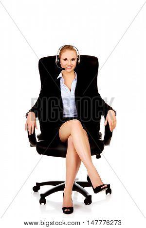 Smiling phone operator in headphones sitting on armchair