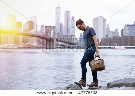 Young entrepreneur with style, going for a walk, wearing boots and a briefcase in New York