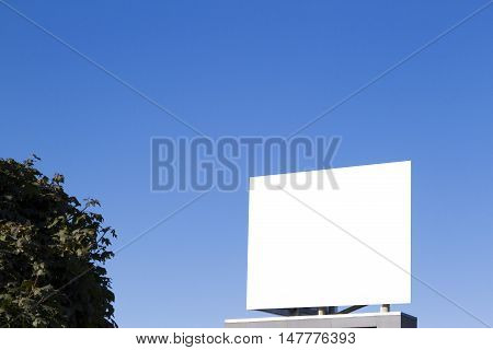 Mock up. Blank billboard in the city against blue sky