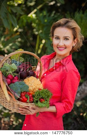 Smiling blonde woman nutritionist holding basket full of vegetables