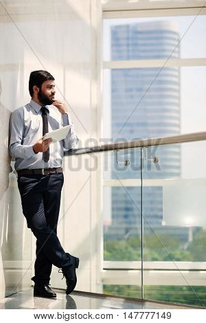 Full-length portrait of pensive businessman looking at the city