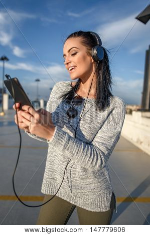 Young stylish woman listening music outdoor by tablet wireless technology