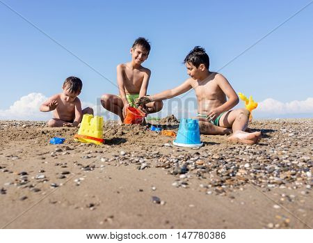 Playful kids on summer beach sand vacation having fun and happy time