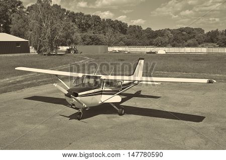 Light private plane on the airfield parked with its doors open - black and white image