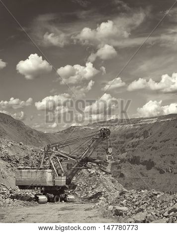 Large excavator on the iron ore opencast on sunny day - black and white image