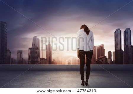 Back view and sad expression asian business woman on the rooftop