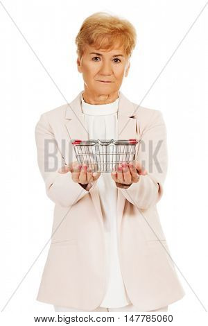 Elderly woman holding small shopping basket