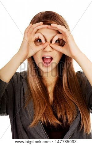 Teenage woman making binoculars hands